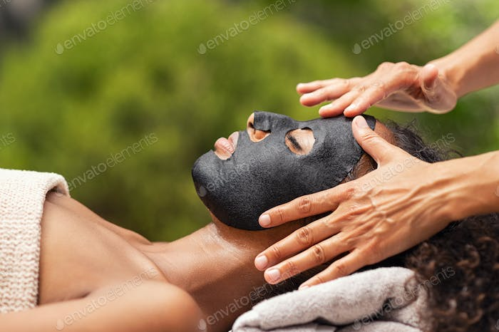 Purifying black beauty mask on woman face