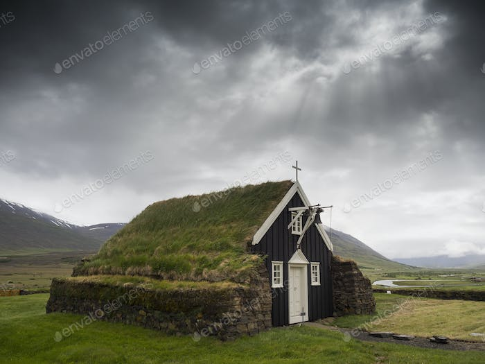 A traditional wooden church with turf roof, earth and grass material on the steep pitched roof.