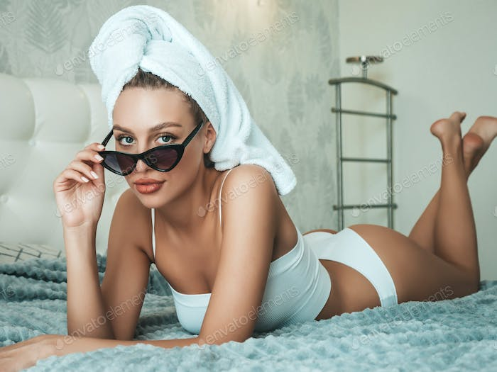 Portrait of young hot woman posing in hotel room