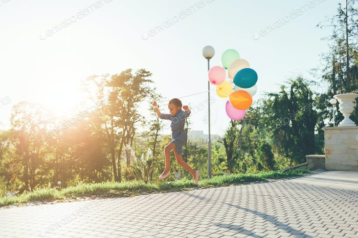 Cute girl holding colorful balloons in the city park, playing, r