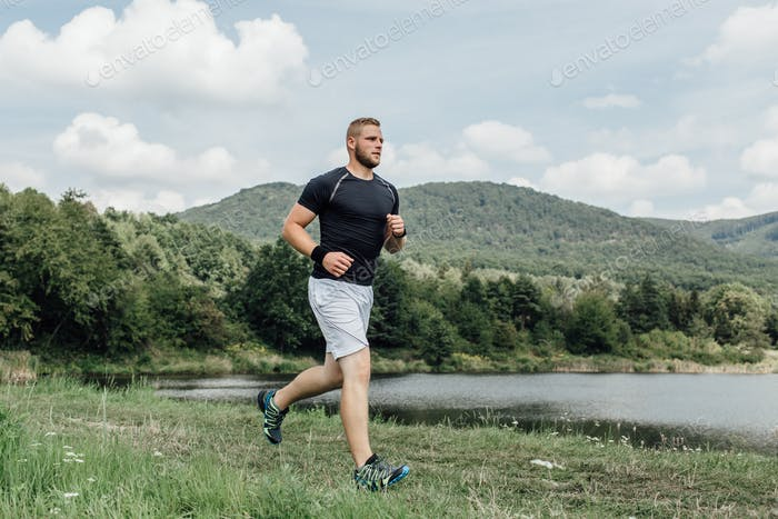 Male runner enjoying running across the country along a pond