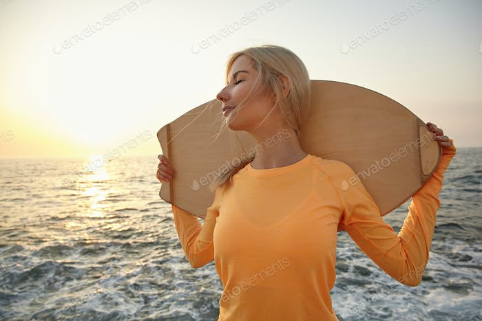 Outdoor close-up of good looking blonde female in orange long sleeve top standing on seafront