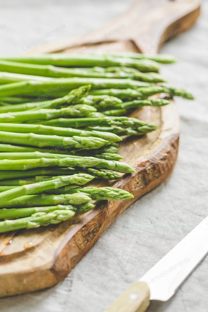 Fresh asparagus on a wooden cutting board. Preparation vegetarian healthy food.