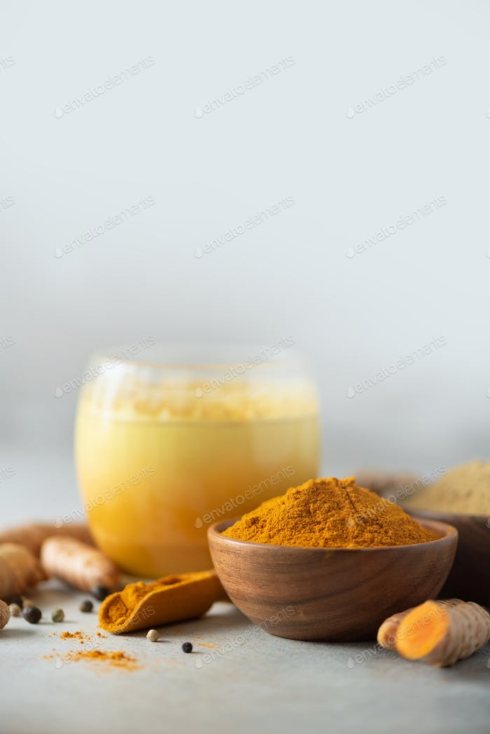 Yellow turmeric latte drink. Golden milk with cinnamon, turmeric, ginger over grey background. Copy