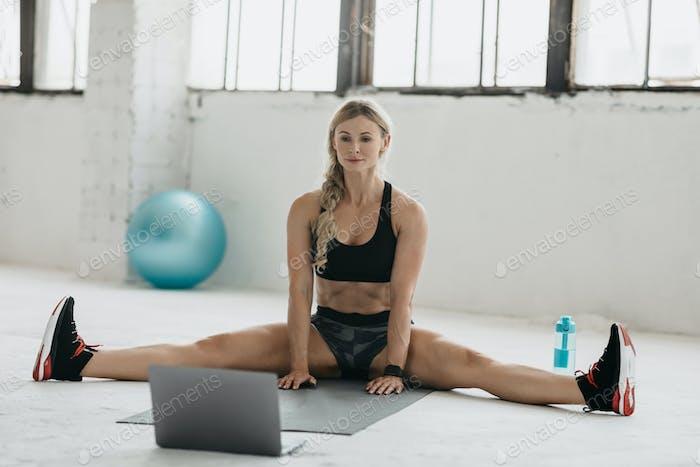 Online-Training im Fitnessstudio. Erwachsene Frau sitzt auf Schnur auf Matte und schaut auf Laptop