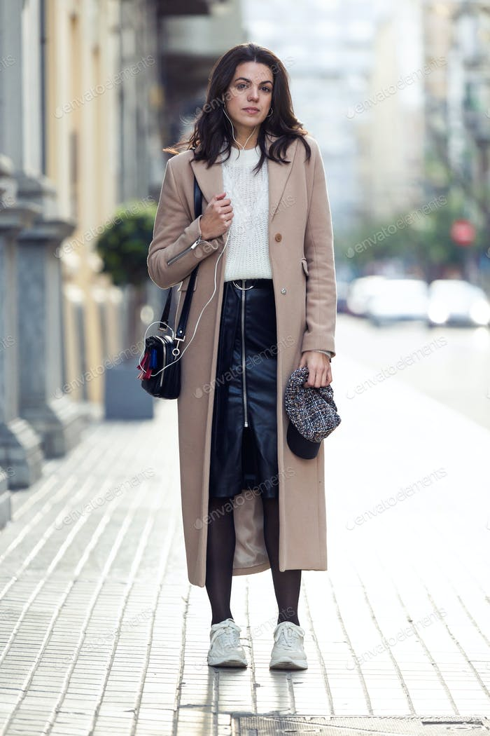 Pretty young woman looking at camera while posing in the street.