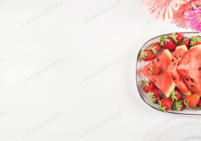 Wassermelonenscheiben auf Tablett auf weißem Holztisch