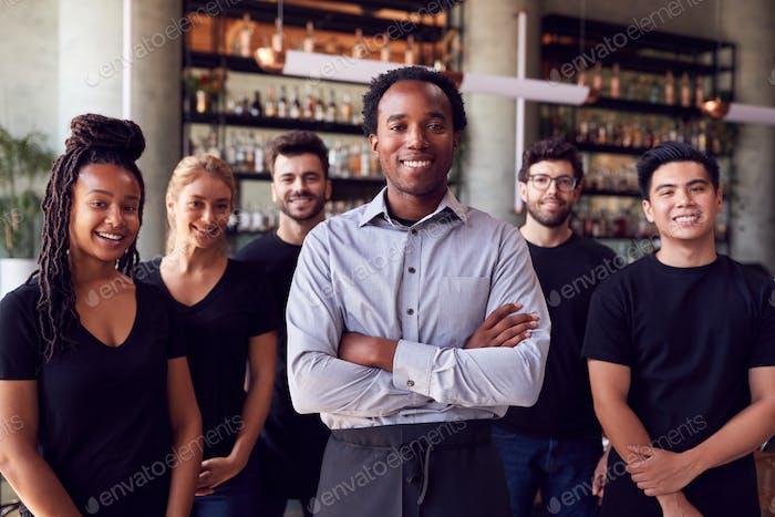 Porträt Von Männlichen Besitzer Von Restaurant Bar Mit Team Von Wartenden Personal Stehen An Zähler