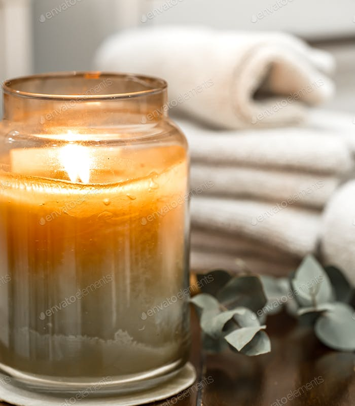 Spa composition with burning candle and bath towels close up.