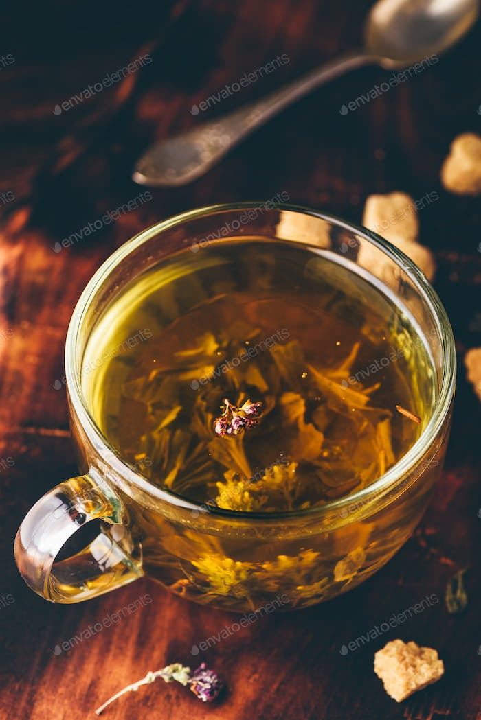 Cup of green tea with brown tea sugar