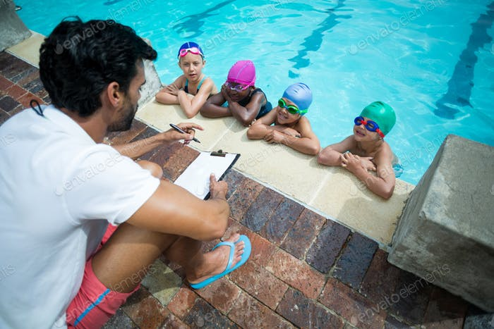 Male instructor with clipboard explaining little swimmers at pooldise