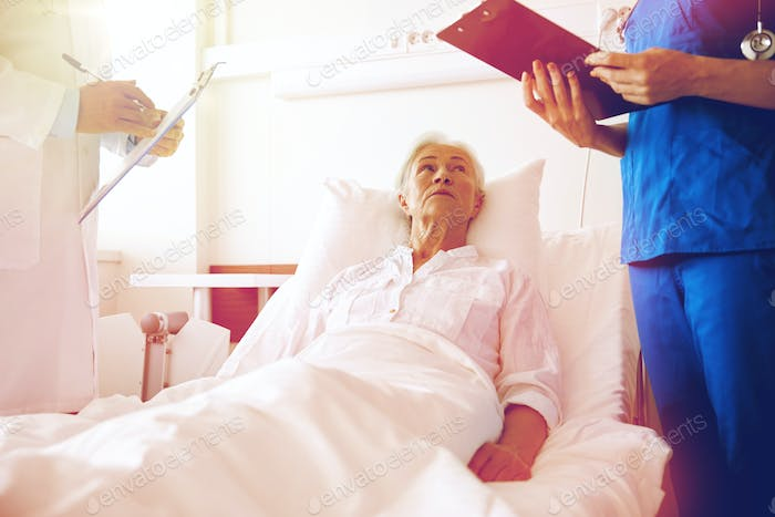 doctor and nurse visiting senior woman at hospital