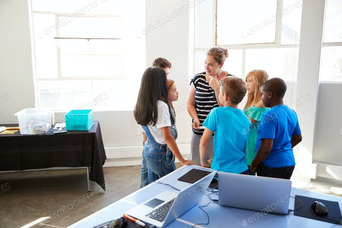 Teacher Talking With Group Of Students In After School Computer Class Learning To Code