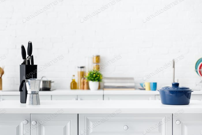 modern white kitchen interior with coffee pot, pot and knives on table