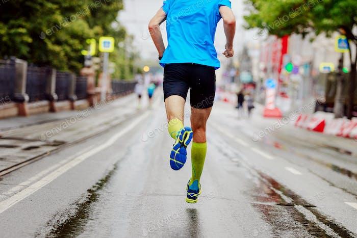 Rücken junger Läufer in gelben Kompressionssocken Laufen urban Marathon
