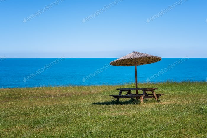 Picnic bench on a green field near the beach