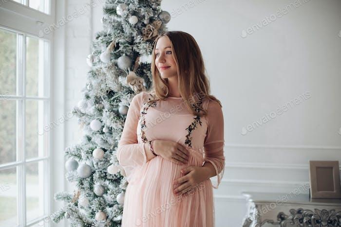 Beautiful sensitive pregnant woman at Christmas. Beautiful pregnant woman against Christmas tree at