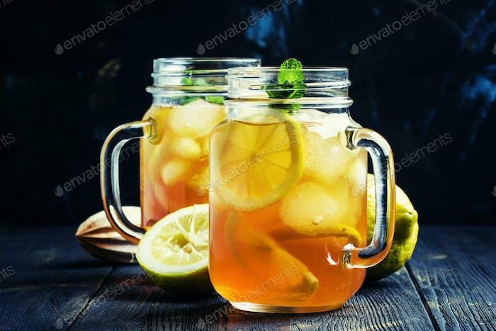 Black ice tea with lemon in a glass jar