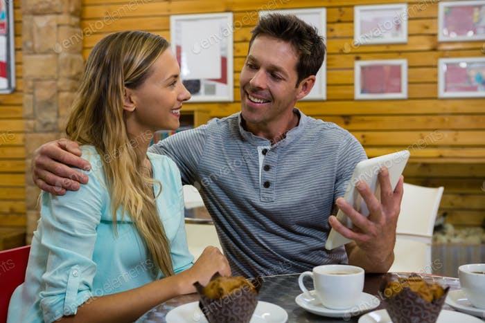 Man showing digital tablet to girlfriend in cafe