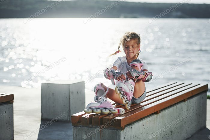 Fixing her skate roller. Cute little girl outdoors near the lake at background