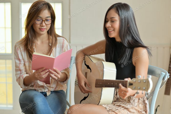 portrait of Two teenage girls playing guitar and practicing singing.