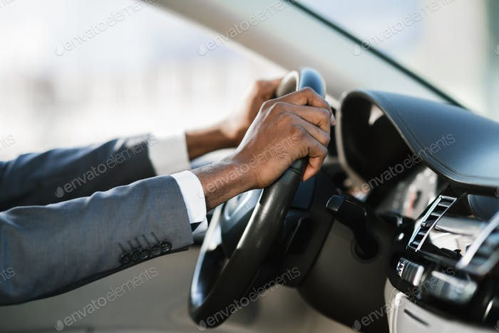 Businessman driving car on highway, holding hands on wheel