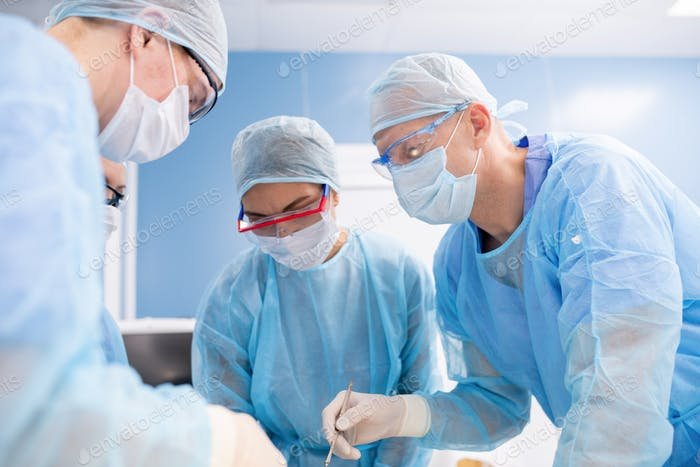 Group of surgeons in masks, gloves and workwear bending over patient