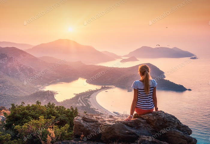 Young woman sitting on the top of rock and looking at the seasho