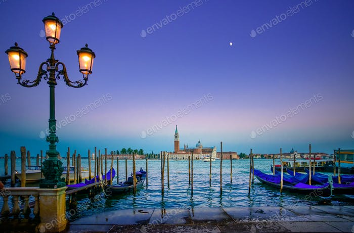 Venice, street lamp and gondolas or gondole on sunset and church on background. Italy