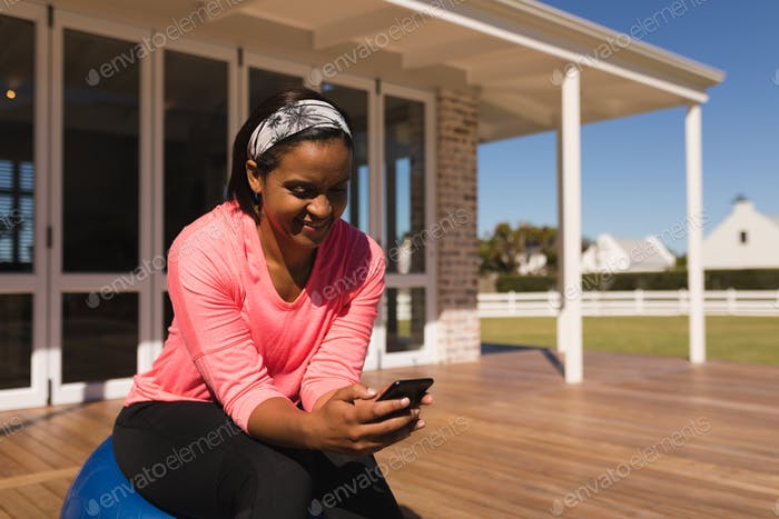 Middle-aged African American woman using mobile phone while sitting on exercise ball