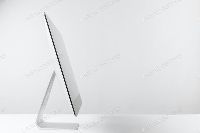 vista lateral del monitor del ordenador de escritorio en blanco
