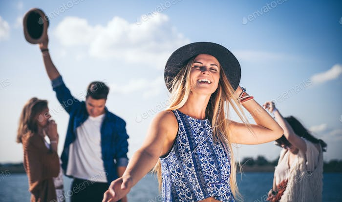 Group of friends dancing and celebrating on beach, boho party