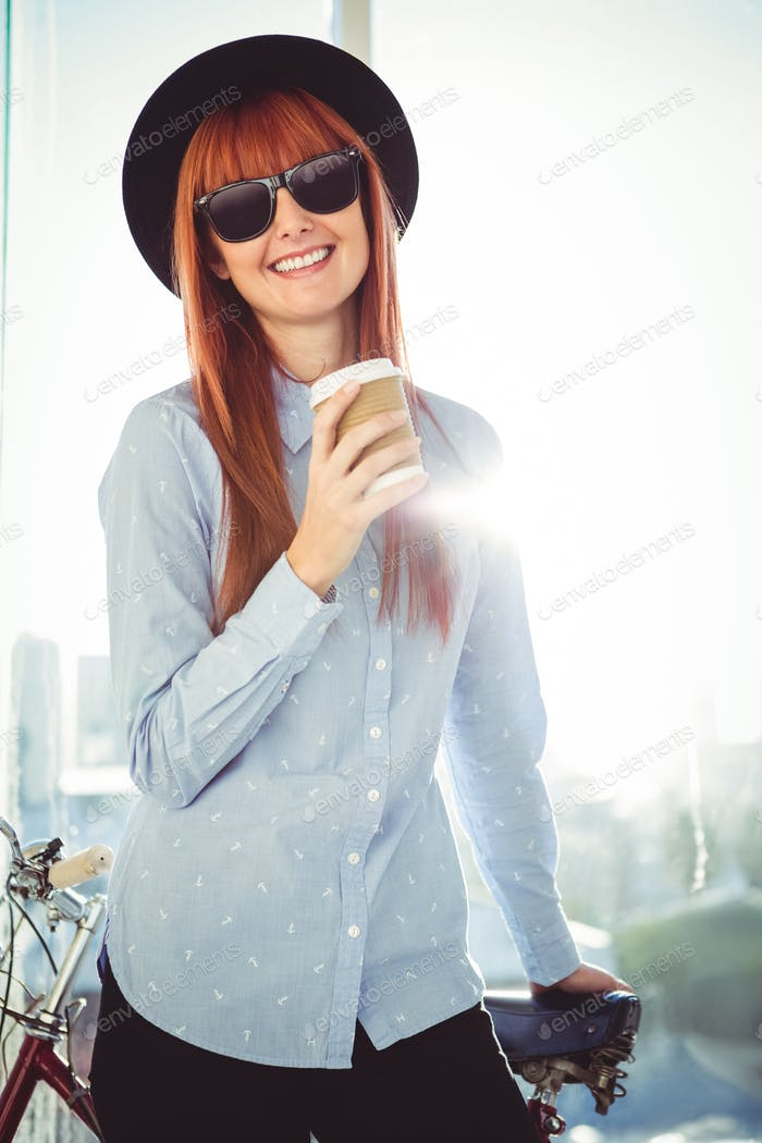 Smiling hipster woman leaning on a bike in a bright room
