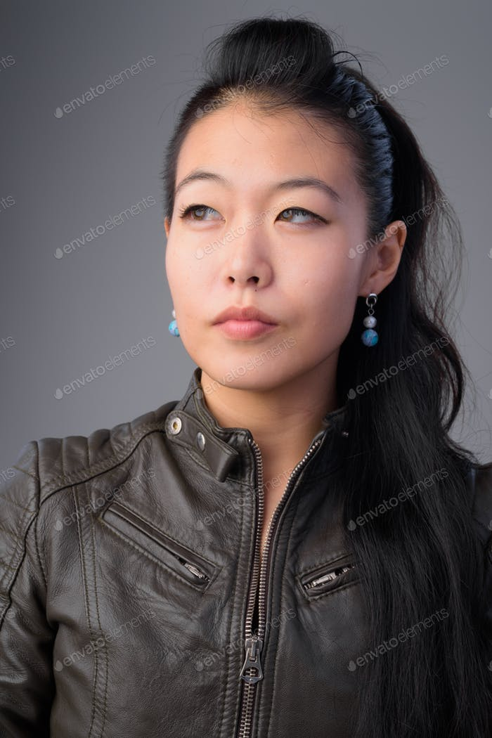 Face of beautiful Asian rebellious woman thinking and looking up