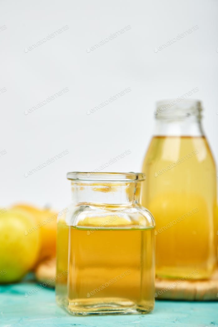 Glass Bottle of apple organic vinegar on blue background