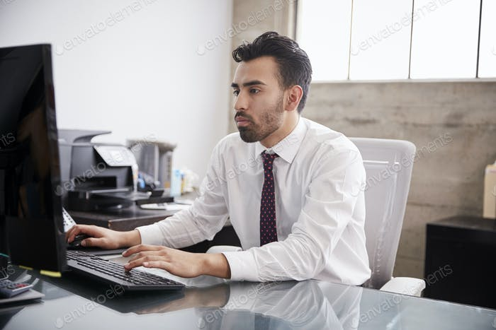 Young Hispanic businessman using computer in an office