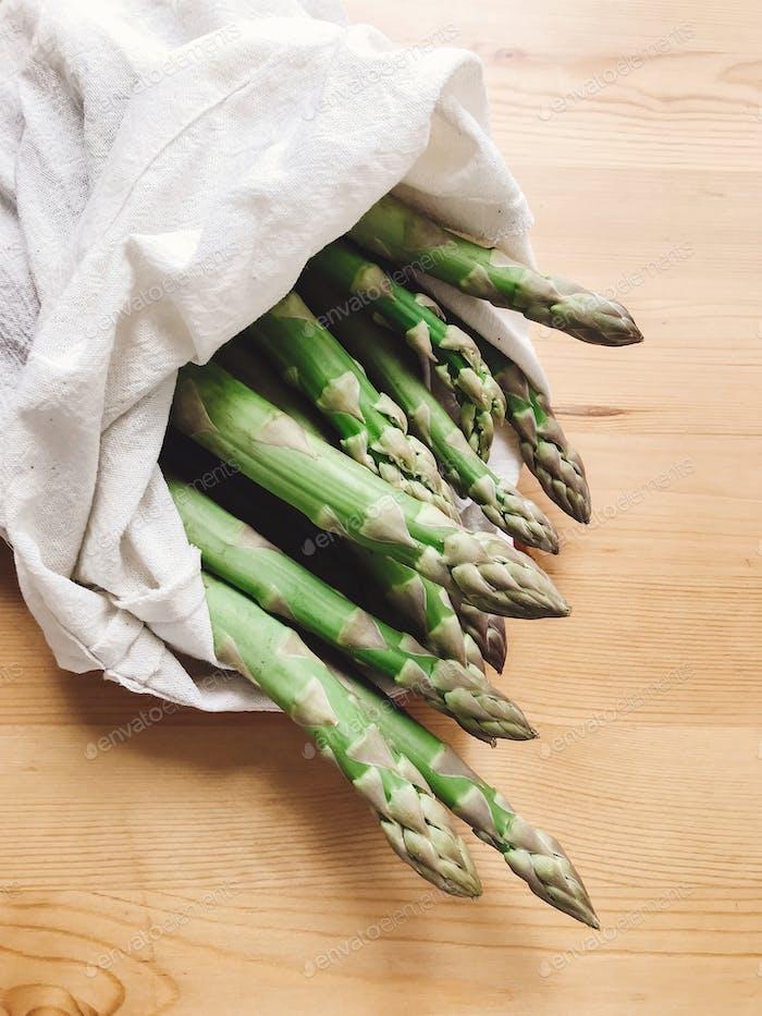 Wiederverwendbare umweltfreundliche Tasche mit frischem Spargel auf Holztisch. Nullmüll Lebensmitteleinkauf