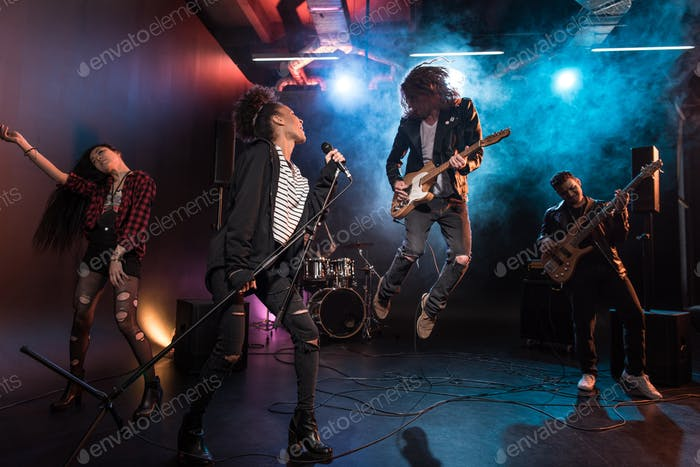 Young multiethnic rock and roll band performing hard rock music on stage