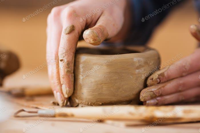 Earthen jar making by hands of woman potter in workshop