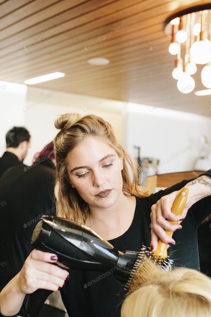 A hair stylist blowdrying a client's blonde hair.