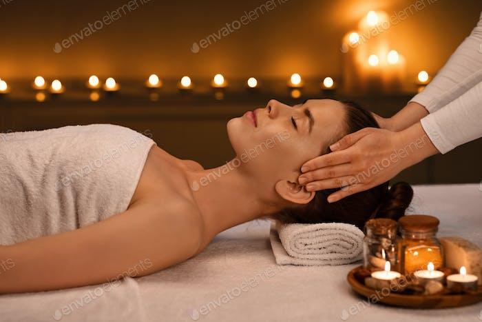 Entspannte junge Frau bekommt Kopfmassage in romantischer Spa-Atmosphäre