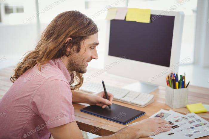 Hipster using graphics tablet while working at computer desk in office