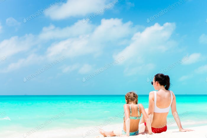 Little cute girl and young mother at tropical beach