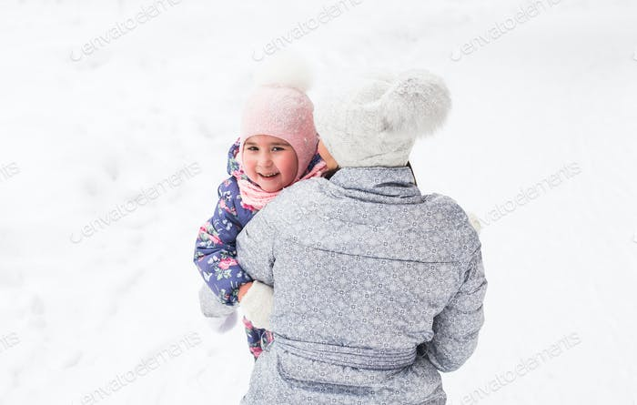 Winter, family and childhood concept - mother is walking with her daughter in snowy forest and