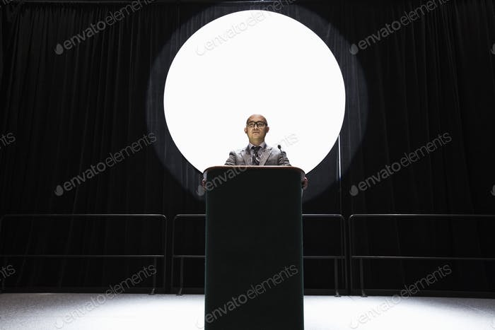An asian businesman standing at a podium giving a talk at a convention.