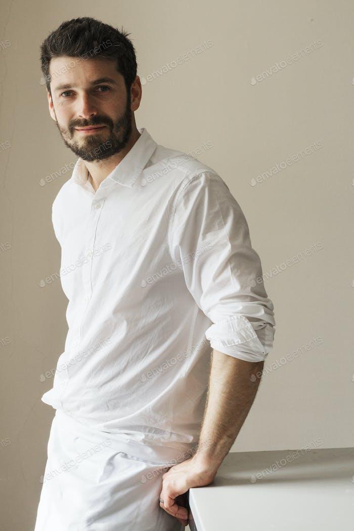 Halb Länge Porträt eines bärtigen Mannes, der eine weiße Schürze trägt, lächelnd in der Kamera.