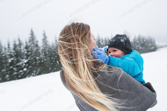 Mother having fun with her son. Winter nature.