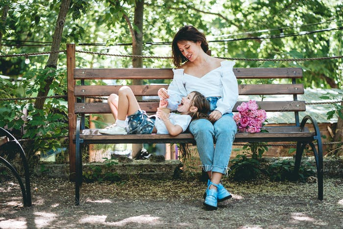 Mom feeds her little daughter ice cream in the park
