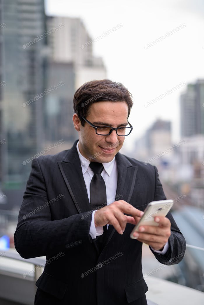 Handsome Persian businessman using phone in the city