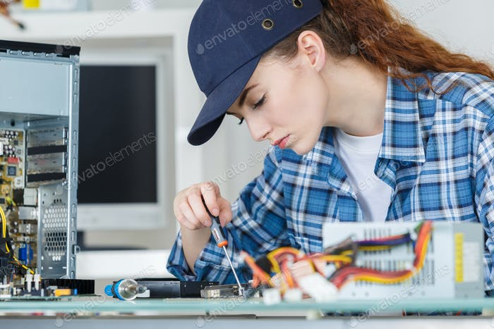 young woman fixing a desktop computer seated at a table